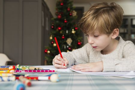 boy coloring at christmastime