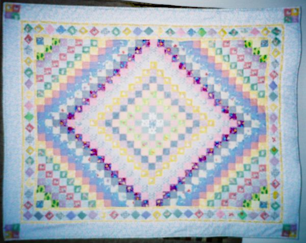 Baby blue quilt with diamond design hanging on a wall.