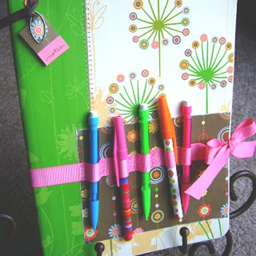 notebook decorated with ribbons, pens, and scrapbook paper