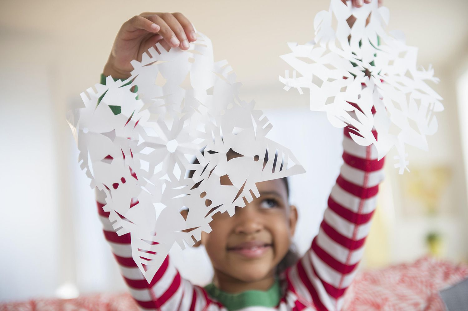 Girl Holding Paper Snowflakes