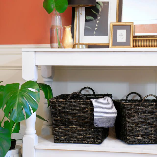 A white console table by an orange wall