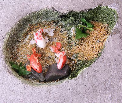 The bottom of a dollhouse scale miniature koi pond is landscaped with sand and artificial plants.