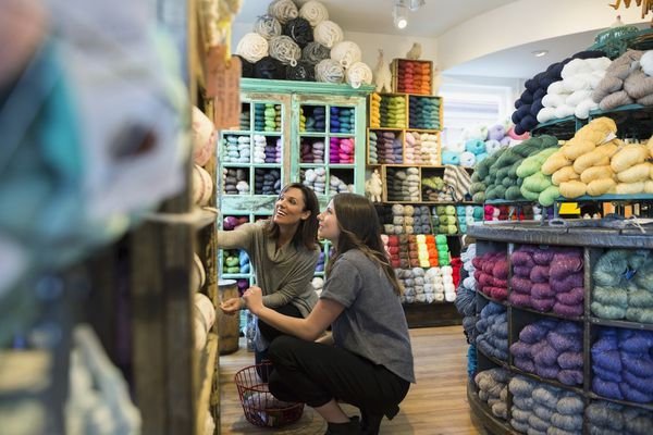 Yarn store owner helping customer look through shelves of colorful yarn.