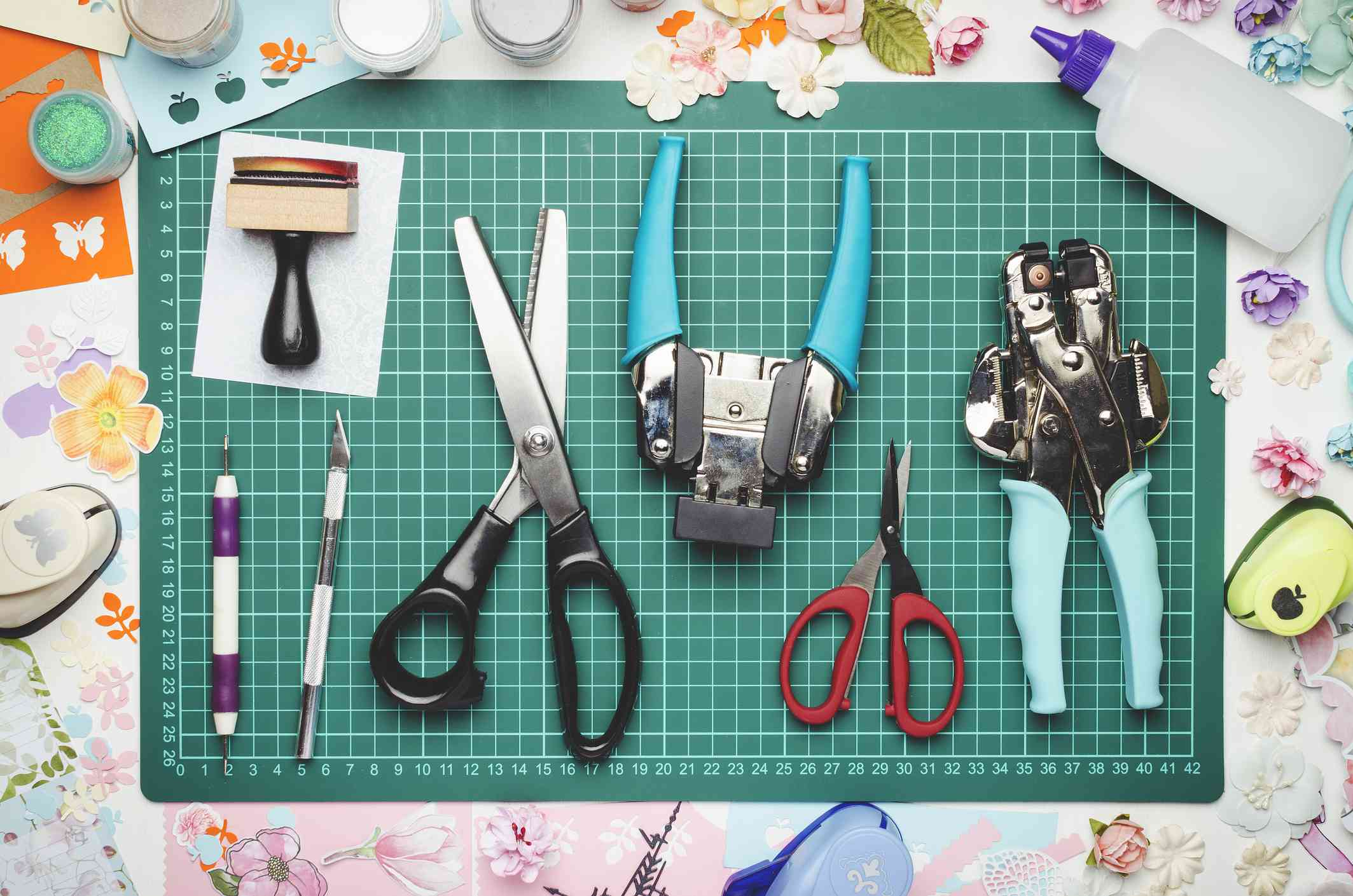 Tools for scrapbooking and creativity on green cutting mat