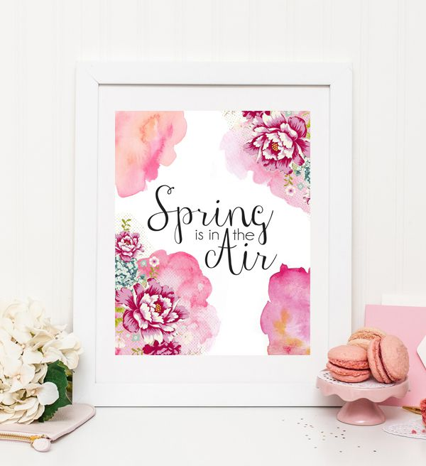 A spring printable framed on a table by flowers and cookies.