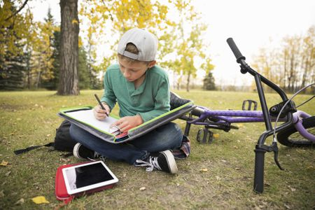 Tween Boy Doing Homework In Autumn Park Hero Images Getty Thanksgiving Word Search Puzzles
