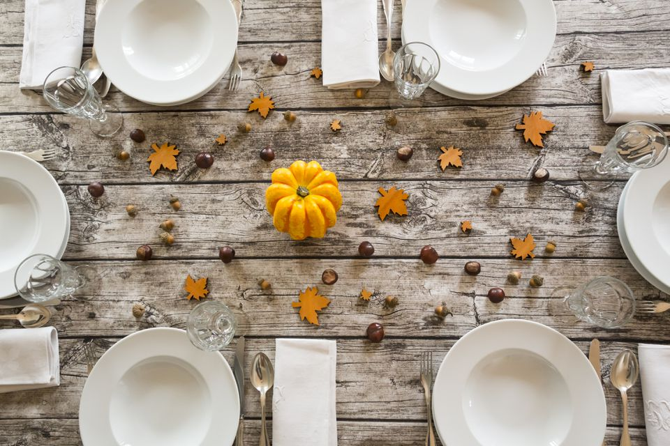 Autumnal laid table with yellow pumpkin, chestnuts and acorns