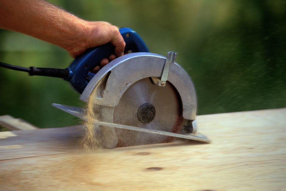 Man cutting wood with circular saw, focus on saw (blurred motion)