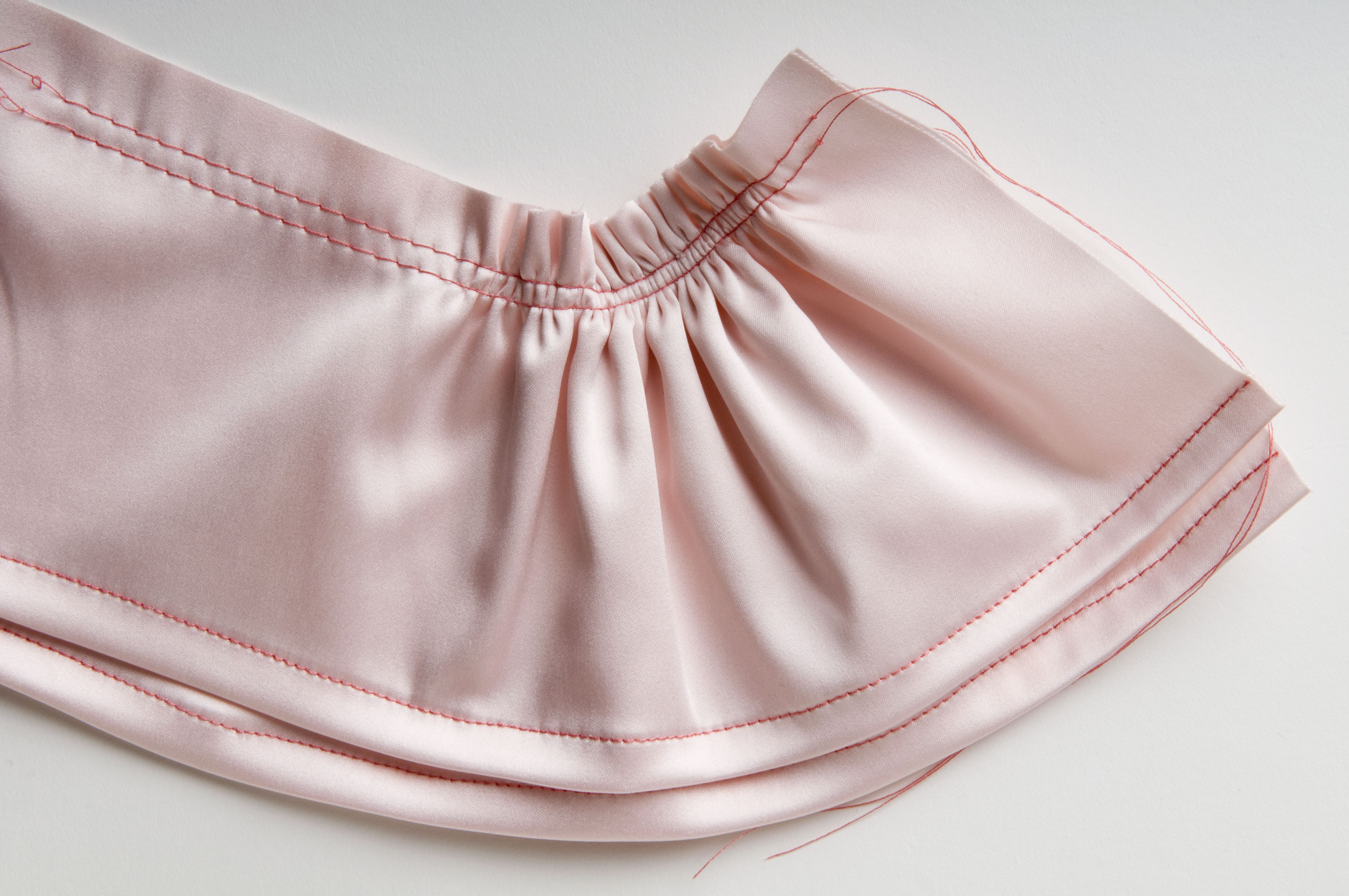 Double ruffle with two rows of gather stitches at top edge and single row of stitches on bottom edge of pink fabric