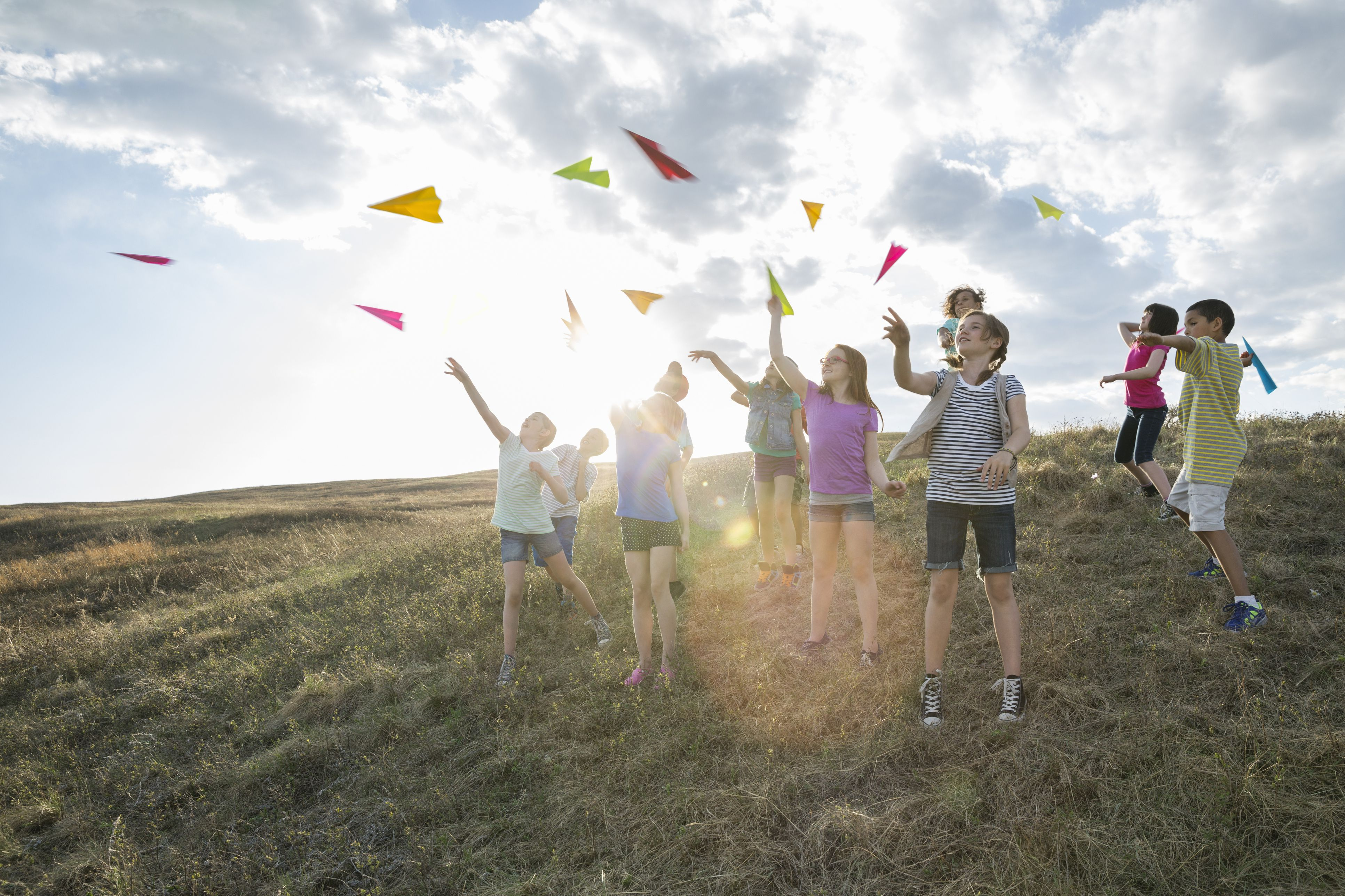 Group of kids outdoors throwing paper airplanes