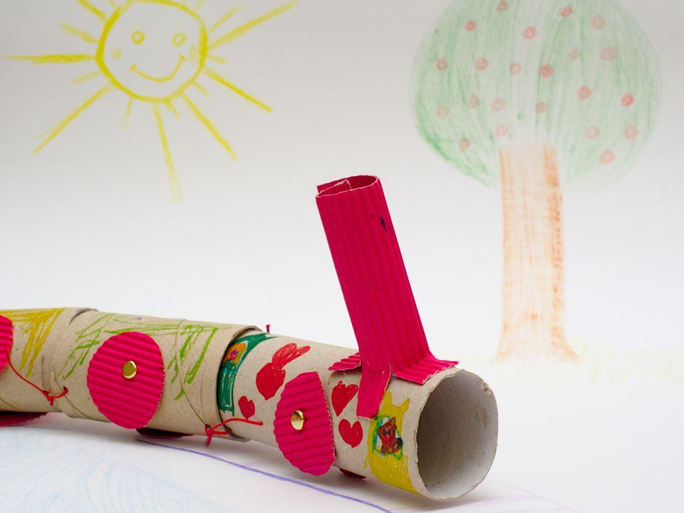 Childish diy train made with cardboard and empty toilet paper rolls isolated on white cardboard painting.