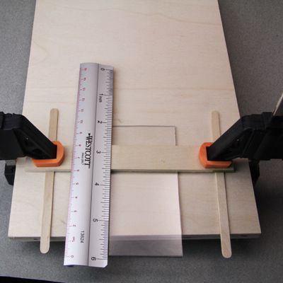 Sheet of 1/16 inch plexiglass set in a simple jig for heat bending using an embossing heat tool.