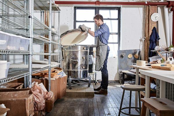 Potter in workshop opening kiln