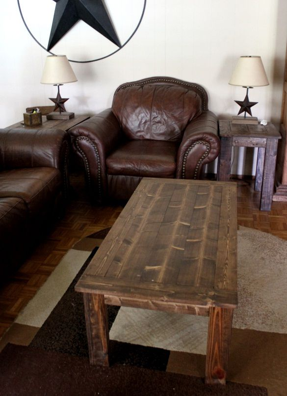 A wooden coffee table in a living room with leather furniture.