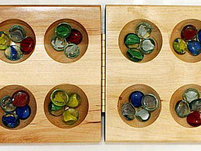 How To Play Mancala Adorable Game With Stones And Wooden Board