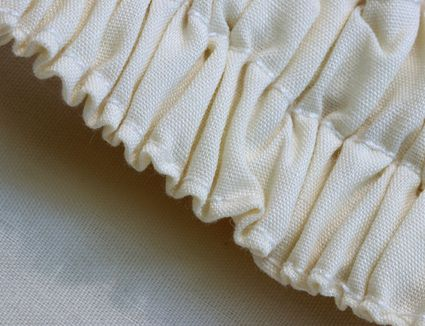Cream colored cotton fabric gathered by elastic creating ruffled patterns