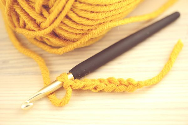 Crochet Hook With Wool On Wooden Table