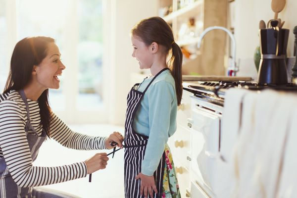 A mom tying her daughter's apron strings in a kitchen