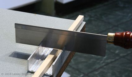 A razor saw ready to cut through a piece of craft wood in a simple miter box.