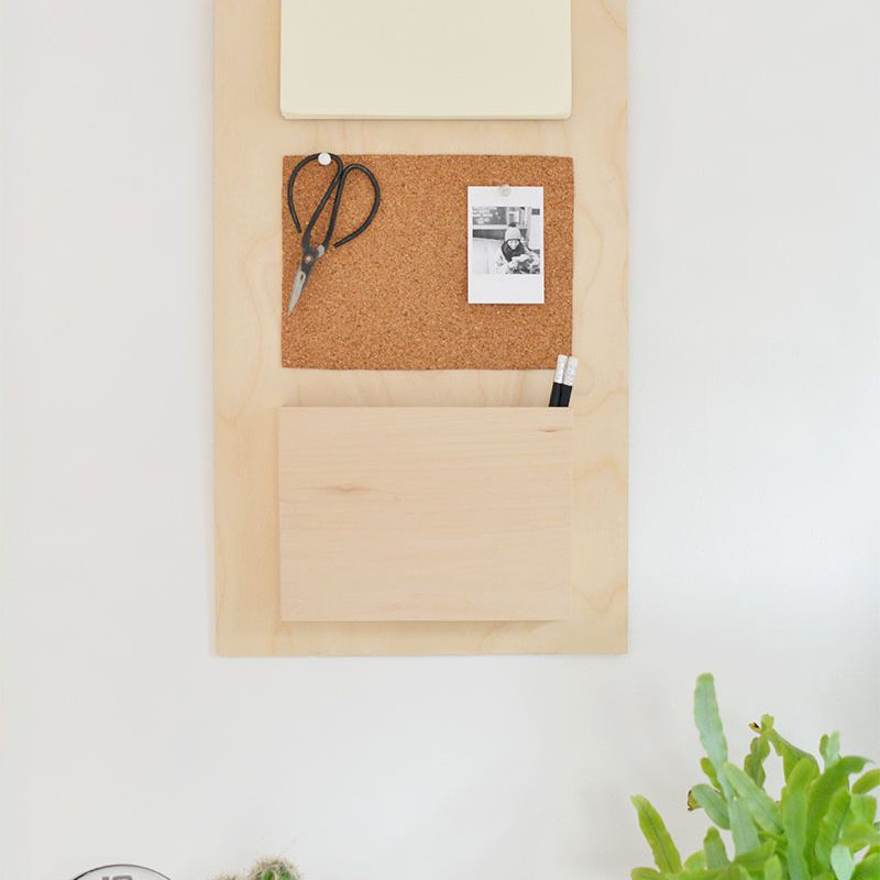 A wood wall organizer with a picture and scissors hanging on it above two plants