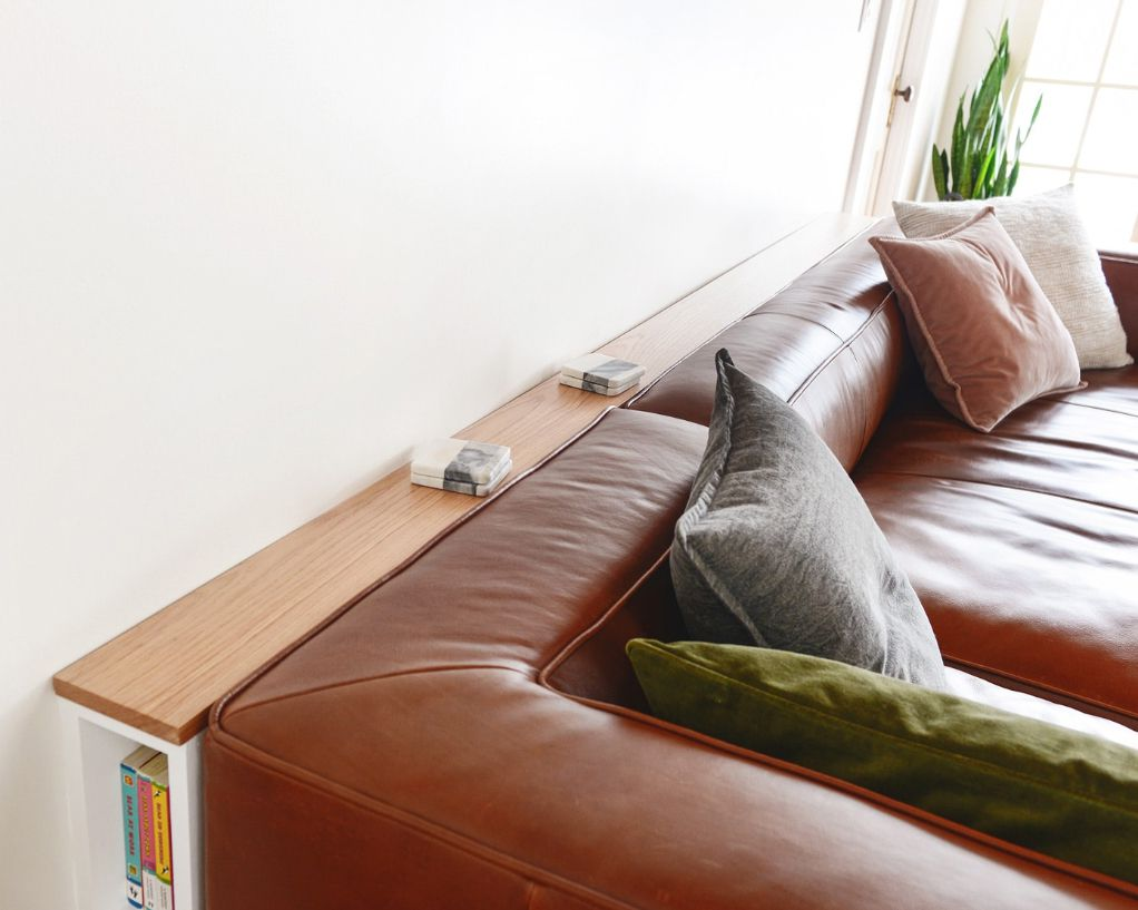 A slim console table behind a couch