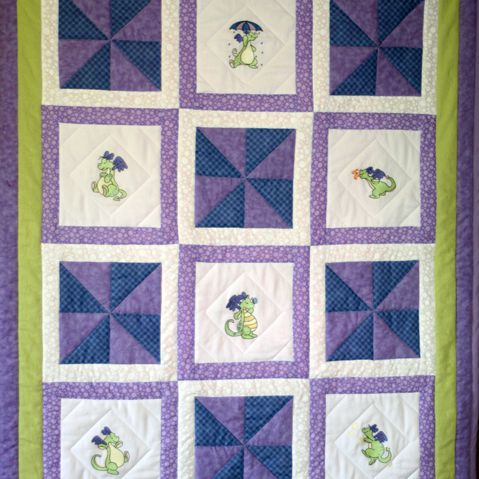 Purple baby quilt with dragons on the squares.