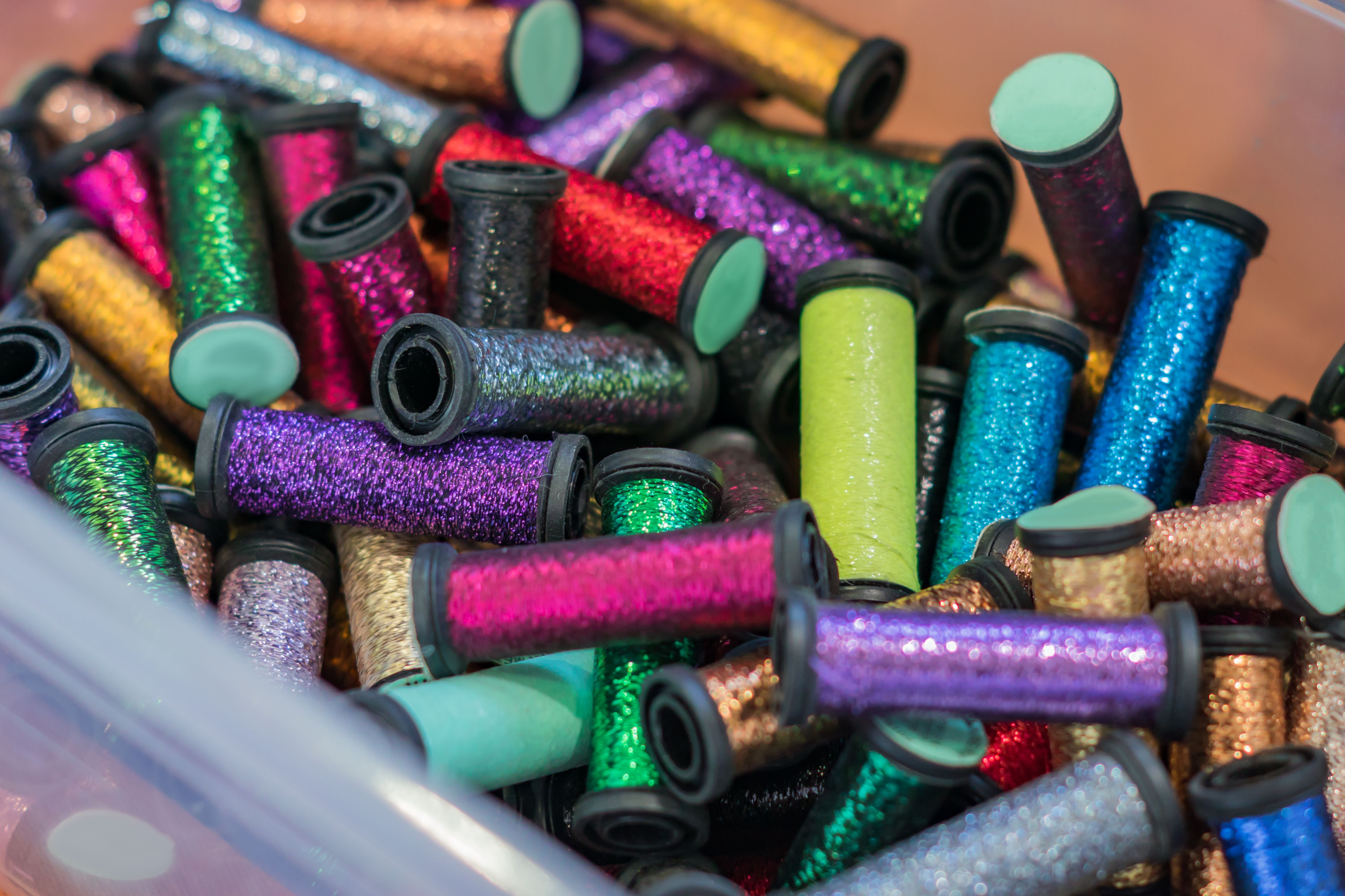Rolls with metallic threads in plastic container in assortment for craft