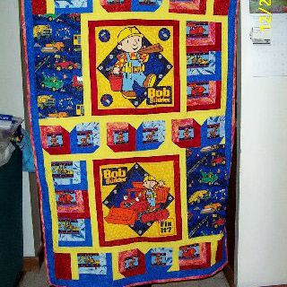 Person holding up blue Bob the Builder quilt.