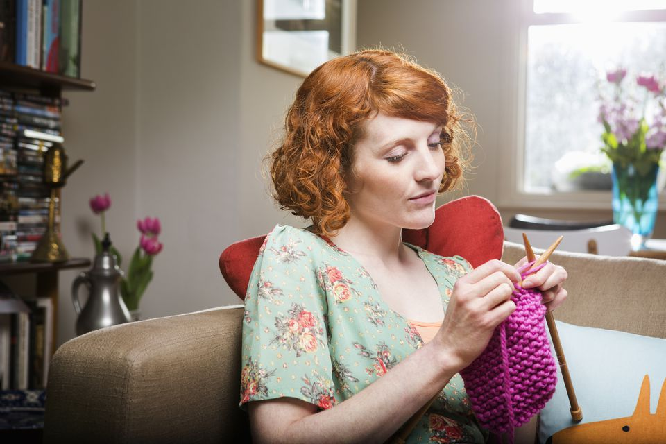 Woman knitting on couch