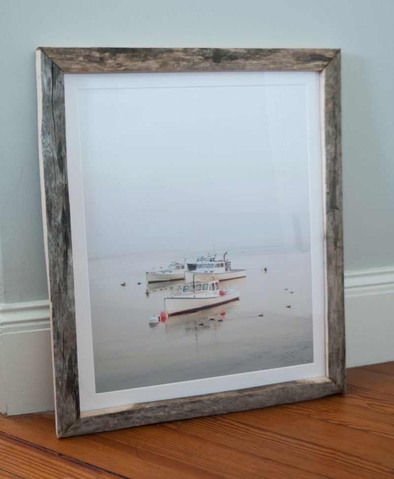 Driftwood picture frame of ships resting on the floor.