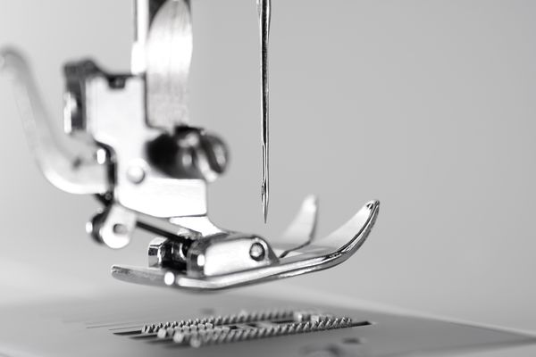 Close-up view of sewing machine pressure foot and needle.