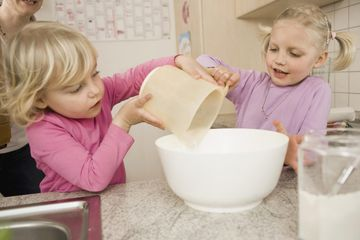 Sisters making cake in kitchen