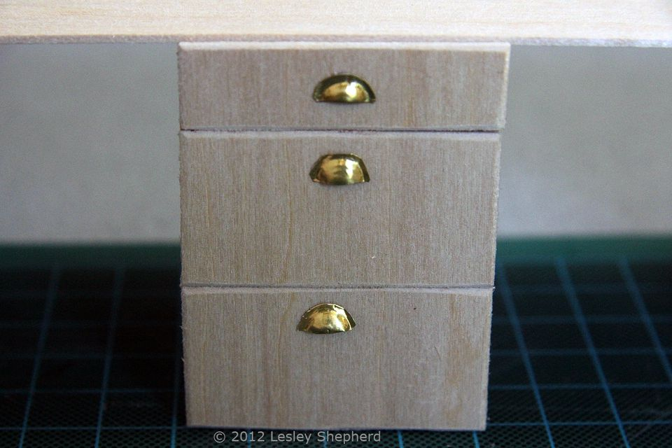 Brass bin pull style handles in dolls house scale on kitchen drawers.