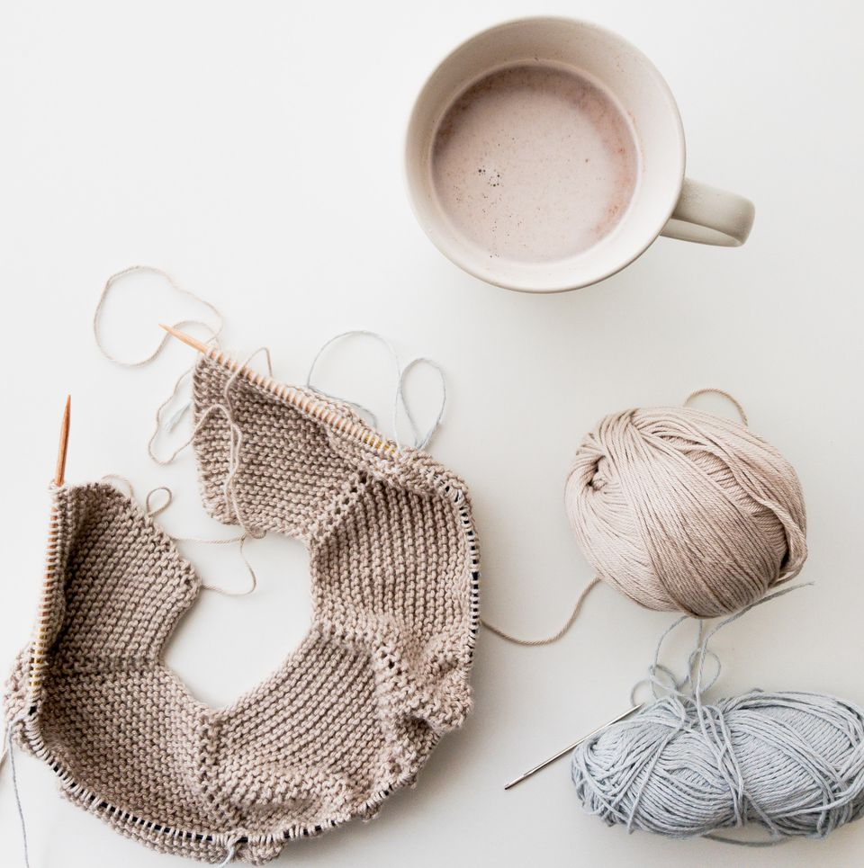 Coffee mug next to yarn and knitting project