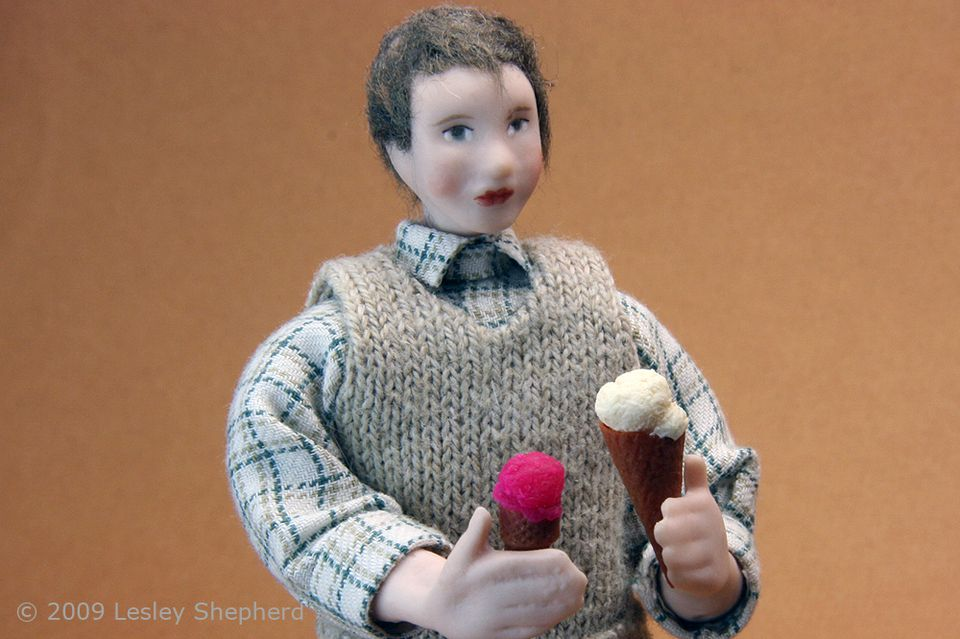 Dollhouse doll holding two ice cream cones.