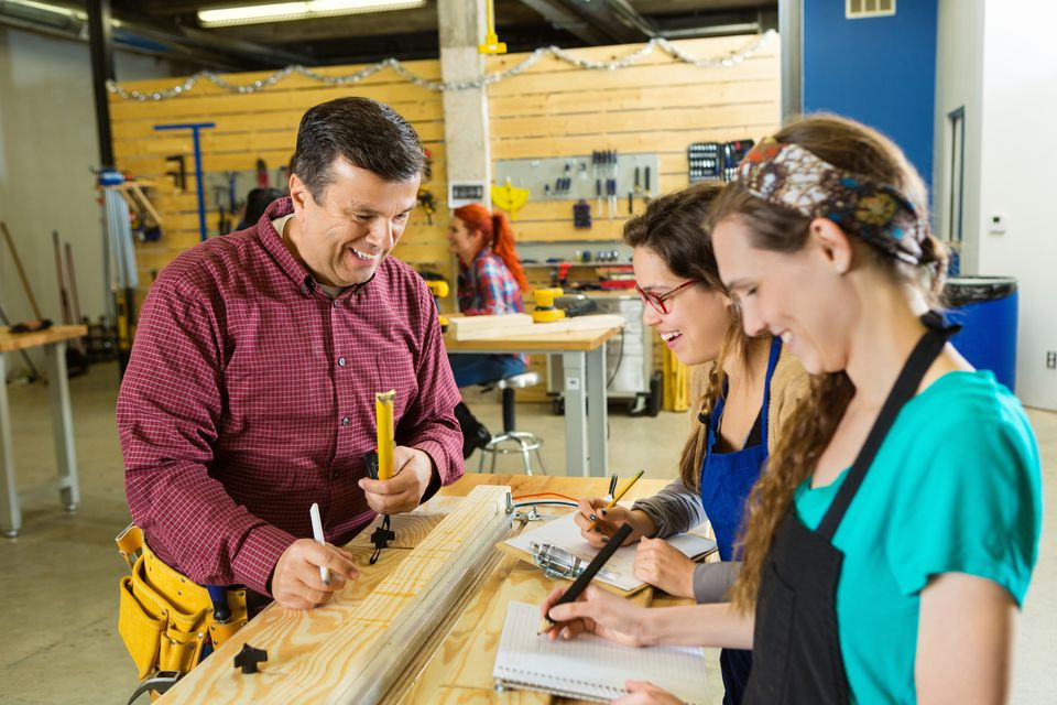 two girls learning cabinetry from a man