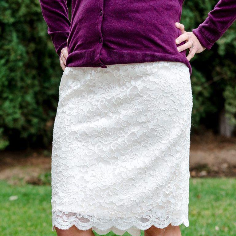 A woman wearing a white lace skirt and a purple shirt