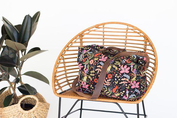 A floral duffel bag on a wicker chair
