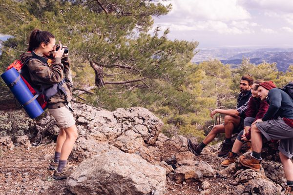 Woman photographing friends on hike