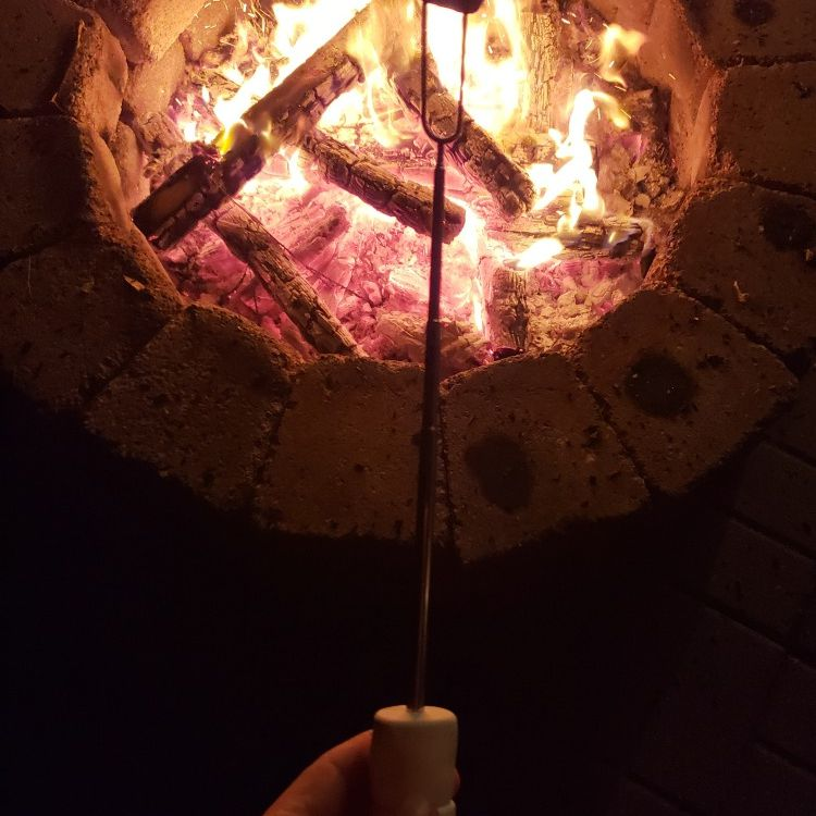 A marshmallow being roasted over a fire pit