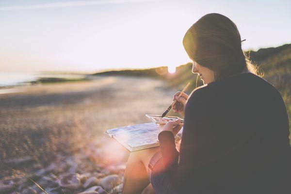 Woman painting on beach