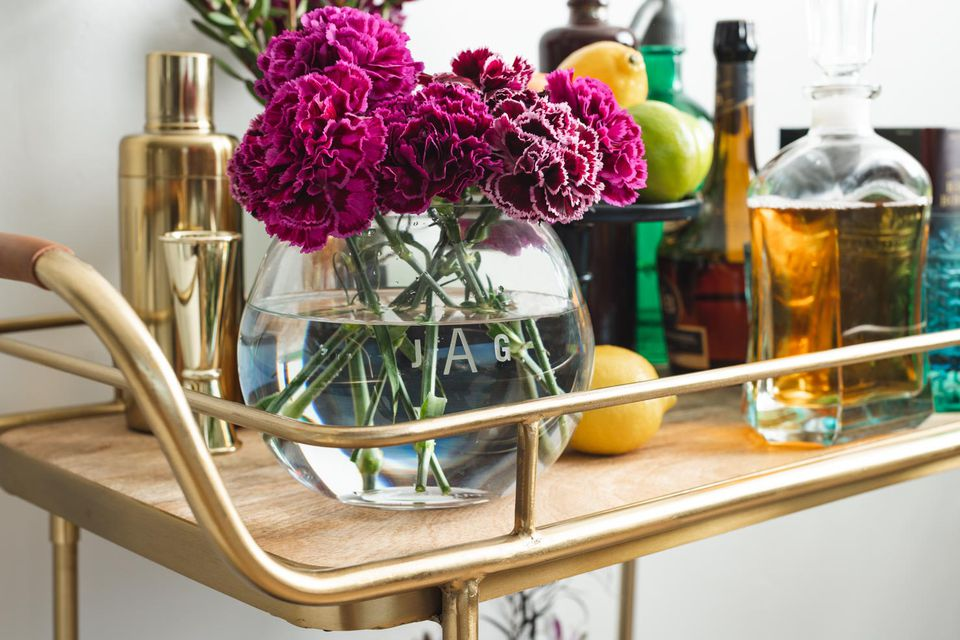 Flowers and bottles on bar cart
