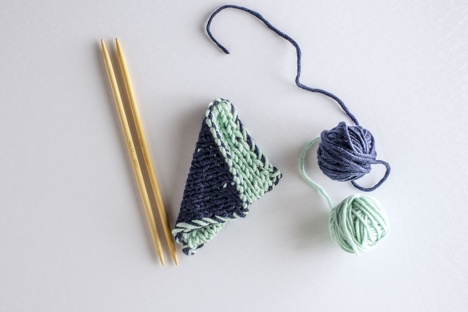 Light blue and navy balls of yarn, wood knitting needles, and knitted fabric on a white surface.