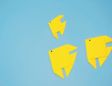 High Angle View Of Yellow Paper Fish On Blue Background