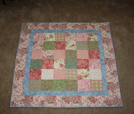 Paisley rose quilt on the floor.