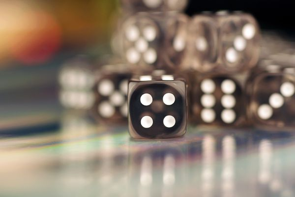Clear Dice With Shallow Depth of Field, Die Displaying Number Four in Focus