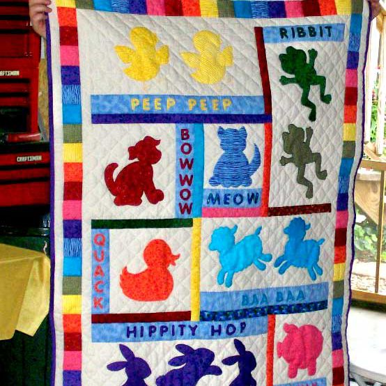 Woman holding baby quilt with animal silhouettes and sounds.