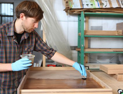Young carpenter varnishing in his workshop