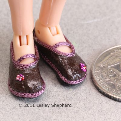 A finished pair of Mary Jane-style tiny doll shoes next to a quarter to show size.