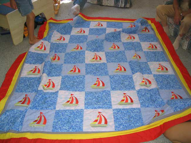 Red, yellow, and blue sailboat quilt on the floor.